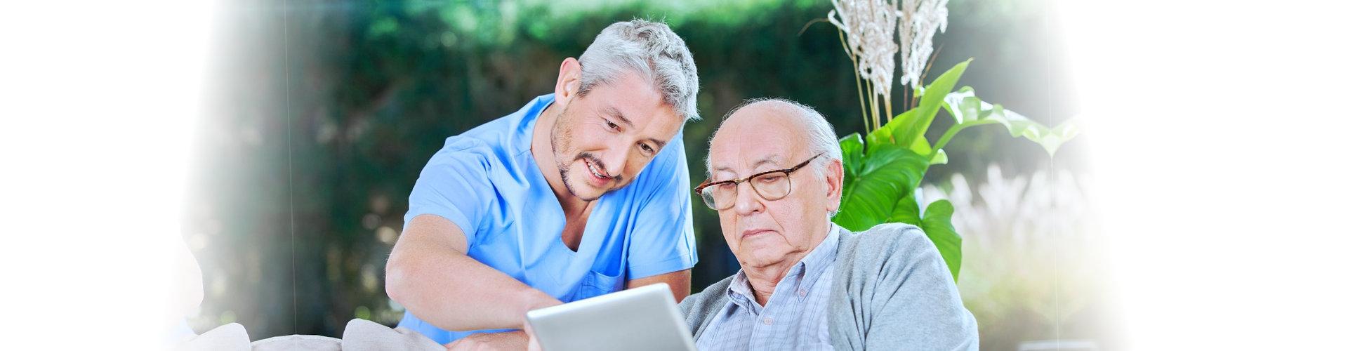 senior man and caregiver using a tablet