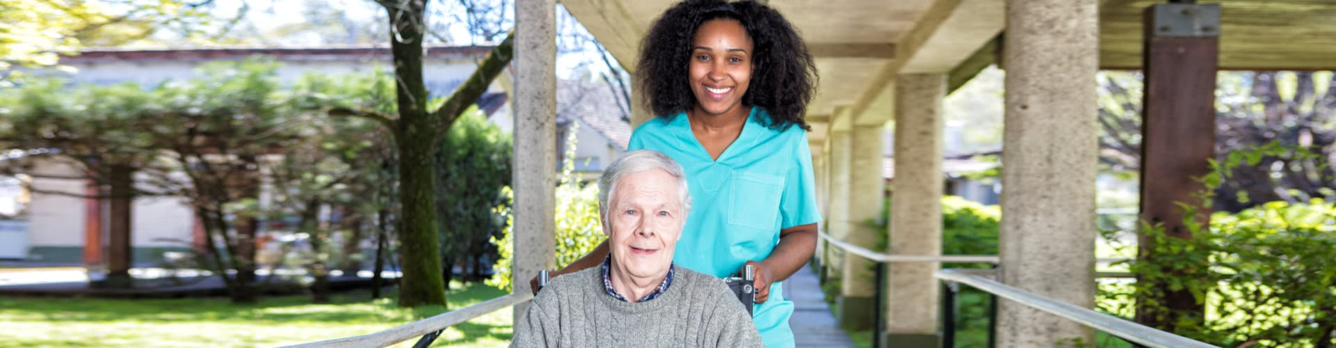 caregiver and senior in wheelchair smiling